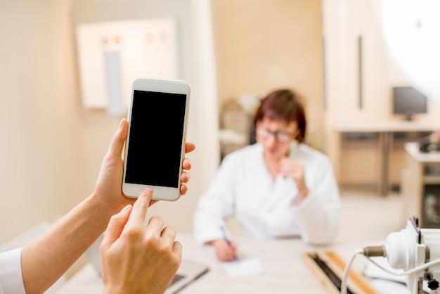 Image de maquette d'un téléphone intelligent sur le fond du bureau ophtalmologique