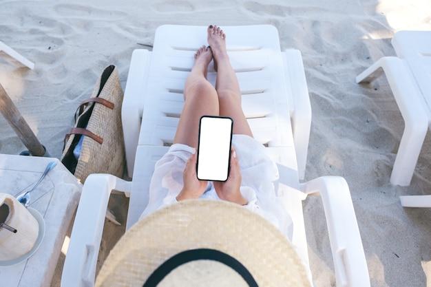 Image de maquette vue de dessus d'une femme tenant un téléphone mobile blanc avec écran de bureau vide tout en fixant sur une chaise de plage sur la plage