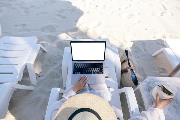 Image de maquette vue de dessus d'une femme tenant et utilisant un ordinateur portable avec écran de bureau vide tout en fixant sur une chaise de plage sur la plage