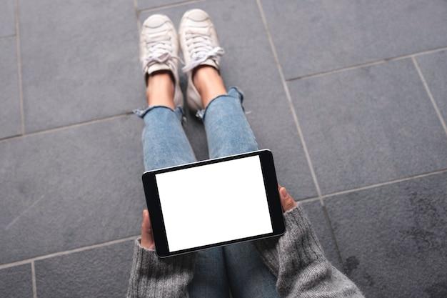 Image de maquette vue de dessus des mains de femme tenant et utilisant un tablet pc noir