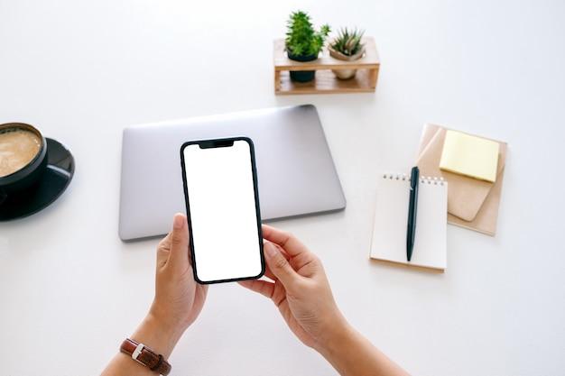Image de maquette vue de dessus des mains tenant un téléphone portable avec écran vide et ordinateur portable sur la table au bureau
