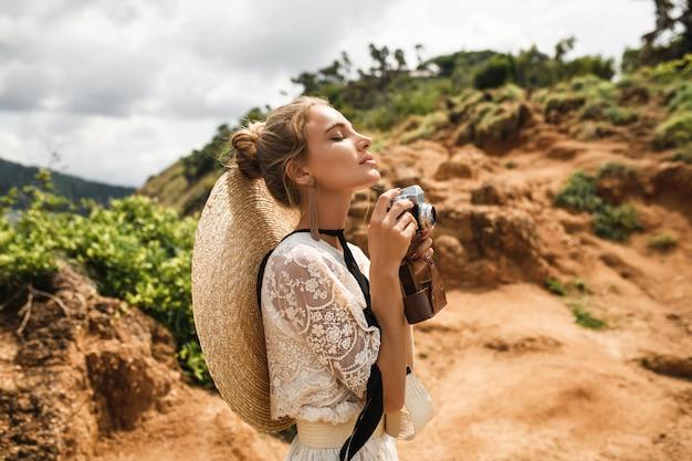Image à la mode d'une femme blonde étonnante avec des cheveux venteux posant avec un appareil photo rétro en plein air sur le coucher de soleil