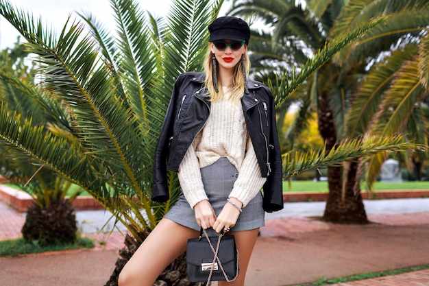 Image de mode en plein air d'une femme élégante et élégante posant dans les rues de barcelone près de palmiers, portant une veste en cuir, une casquette, des lunettes de soleil rétro, un petit sac, un pull confortable blanc et des bijoux à la mode, une mini jupe.