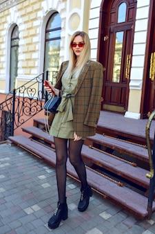 Image de mode en plein air d'une superbe femme mannequin blonde posant dans la rue de paris, tenue à la mode avec une veste moderne surdimensionnée, automne printemps mi-saison, couleurs chaudes aux tons.