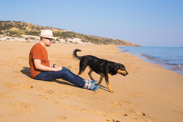 Image de mode de vie en plein air d'un homme voyageant avec un chien mignon sur la plage. concept de tourisme et d'animaux de compagnie.