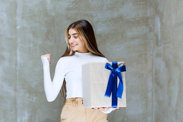 Image d'un modèle de fille tenant une boîte présente avec arc isolé sur pierre