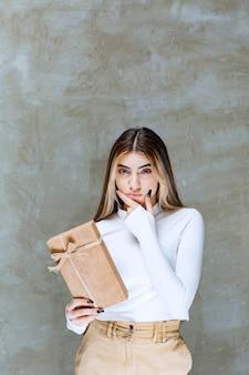 Image d'un modèle de fille tenant un papier présent sur la pierre