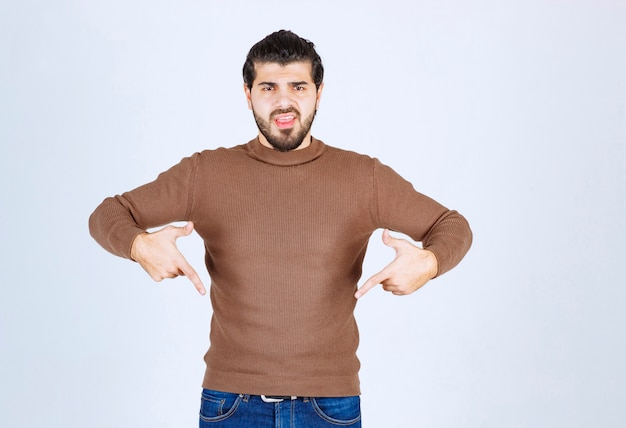 Image d'un modèle de jeune bel homme debout et pointant vers le bas. photo de haute qualité