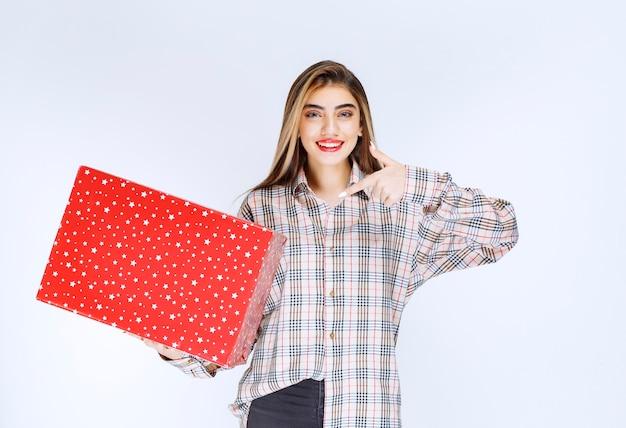 Image d'un modèle de jeune femme debout et pointant du doigt une boîte cadeau rouge.