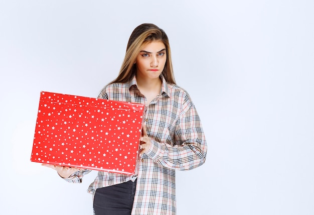 Image d'un modèle de jeune femme debout et tenant une boîte cadeau rouge.