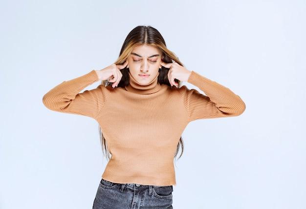 Image d'un modèle de jeune femme en pull marron couvrant les oreilles avec les doigts.