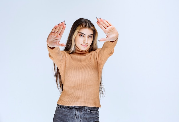 Image d'un modèle de jeune femme en pull marron debout et faisant un panneau d'arrêt.