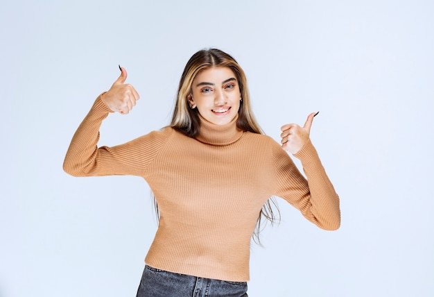 Image d'un modèle de jeune femme en pull marron debout et montrant les pouces vers le haut.