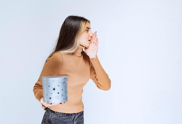 Image d'un modèle de jeune femme en pull marron debout et posant avec une boîte-cadeau.