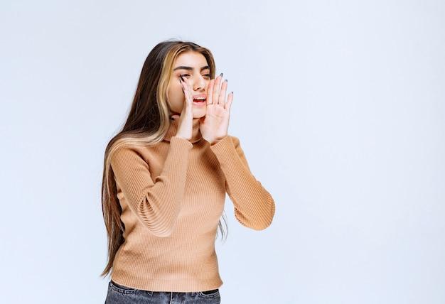 Image d'un modèle de jeune femme en pull marron debout et posant.