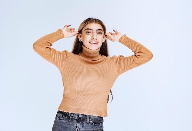 Image d'un modèle de jeune femme en pull marron debout et tenant les oreilles.