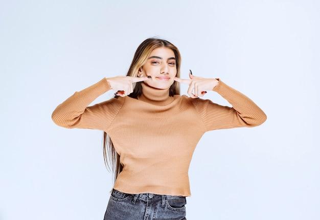 Image d'un modèle de jeune femme en pull marron debout et touchant les joues.