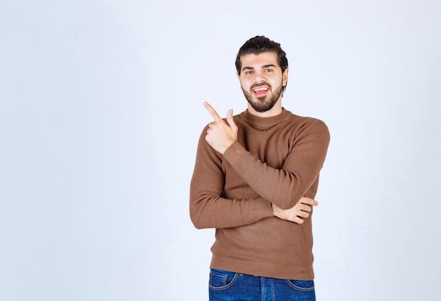 Image d'un modèle de jeune homme souriant debout et pointant vers le haut avec un index. photo de haute qualité