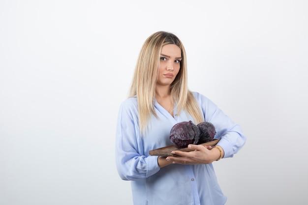 Image d'un modèle jeune jolie femme debout et tenant le chou.