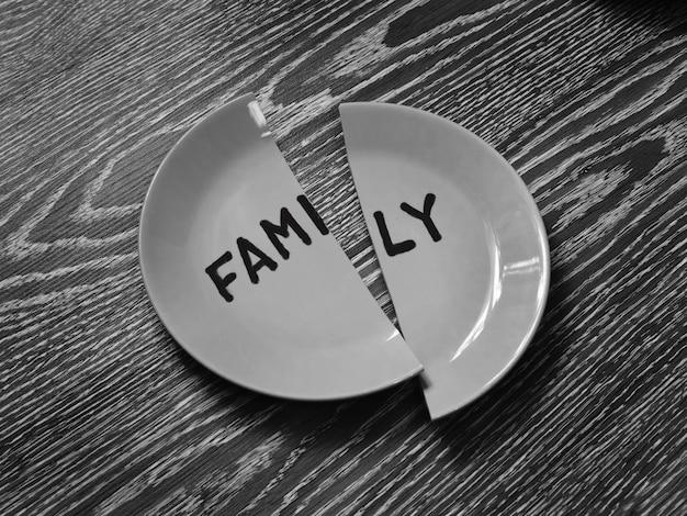 Image monochrome. assiette cassée avec la famille d'inscription. notion de divorce