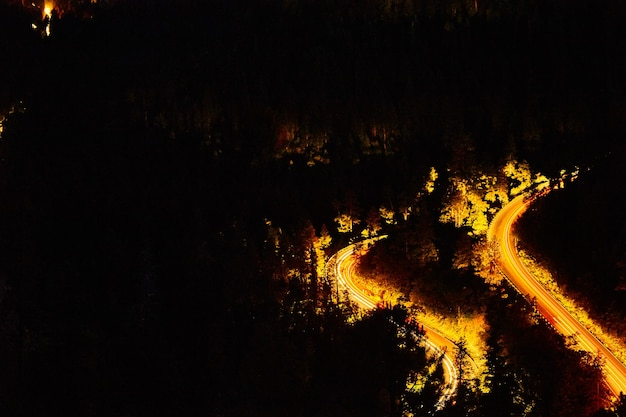 Image de montagne la nuit avec des voitures roulant sur une route sinueuse