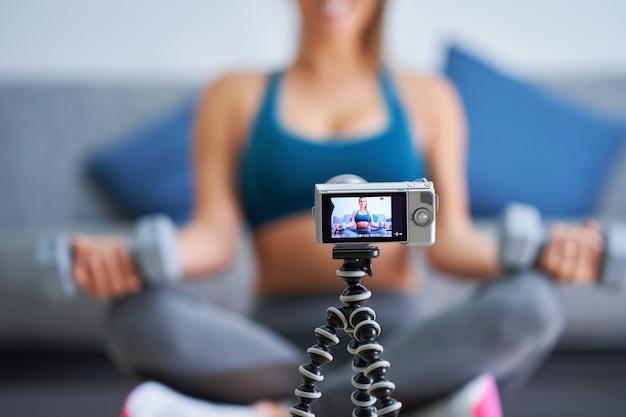 Image montrant un influenceur de vlogger de fitness enregistrant une vidéo de didacticiel en direct
