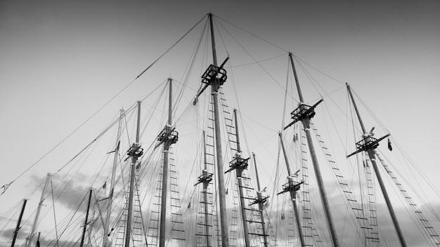 Image en noir et blanc de beaucoup de hauts mâts en bois de navires historiques dans le port maritime