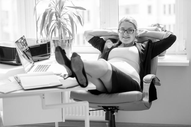 Image en noir et blanc d'une femme d'affaires enceinte souriante assise sur une chaise et tenant des jambes sur une table de bureau