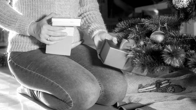 Image en noir et blanc d'une femme mettant des cadeaux et des cadeaux de noël sous l'arbre de noël dans le salon