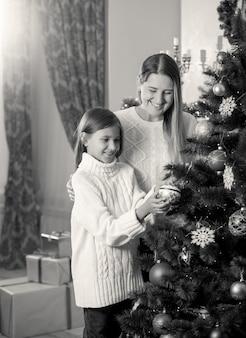Image en noir et blanc de fille aidant la mère à décorer l'arbre de noël