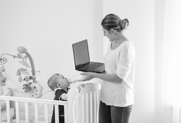 Image en noir et blanc d'une jeune femme d'affaires travaillant à la maison et donnant du lait à son bébé