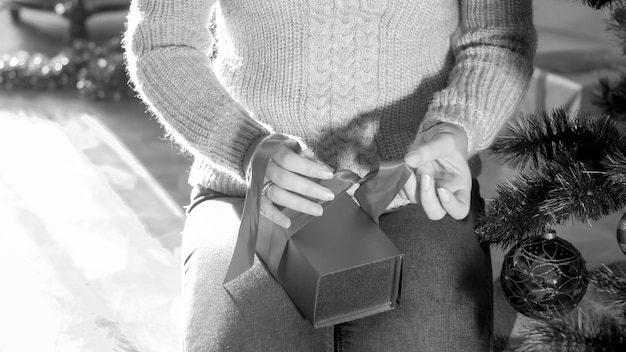Image en noir et blanc d'une jeune femme assise à côté d'un arbre de noël et attachant un nœud de ruban sur un cadeau de noël