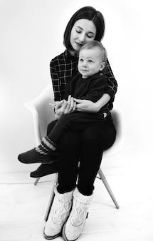 Image en noir et blanc de jeune mère étreignant son petit fils