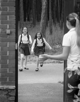 Image en noir et blanc d'une jeune mère rencontrant sa fille après l'école dans la cour de la maison