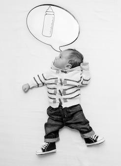 Image en noir et blanc d'un mignon petit garçon allongé sur le lit et rêvant d'une bouteille de lait
