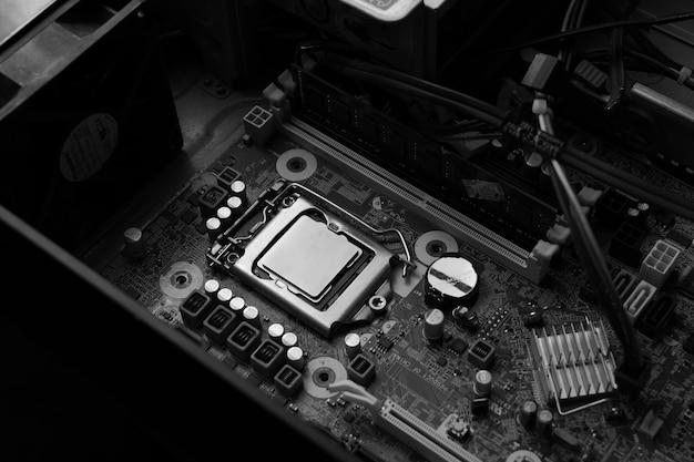 Une image en noir et blanc d'un pc ouvert pour regarder à l'intérieur contenant le processeur et la carte mère et