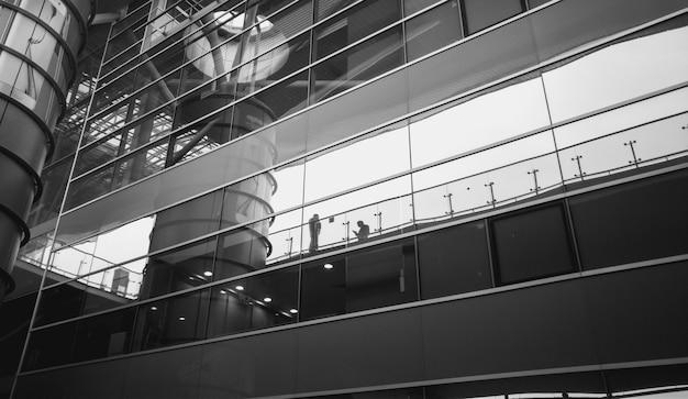 Image en noir et blanc de personnes se reflétant dans un bâtiment en verre moderne