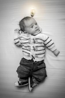 Image en noir et blanc d'un petit garçon intelligent avec une ampoule rougeoyante au-dessus
