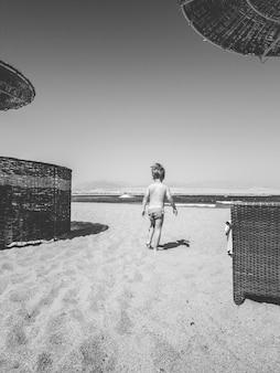 Image en noir et blanc d'un petit garçon marchant sur la plage de la mer entre des chaises longues et des parasols. enfant se détendre et passer du bon temps pendant les vacances d'été.