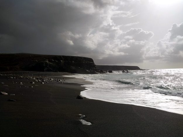 Image en noir et blanc de vagues calmes sur la côte
