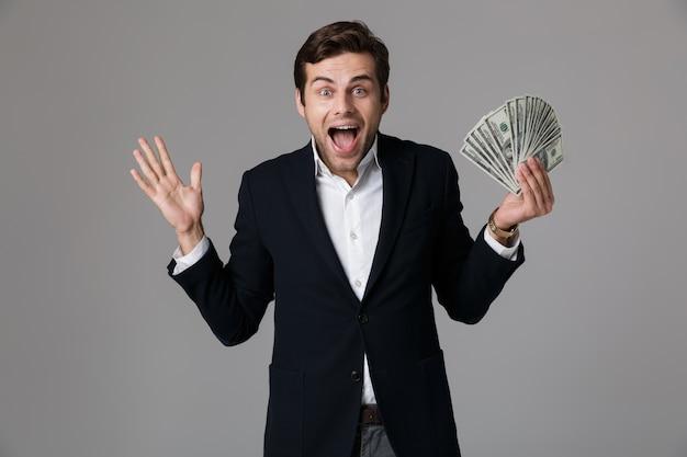Image of attractive businessman 30 s in suit smiling and holding fan d'argent en billets en dollars, isolé sur mur gris