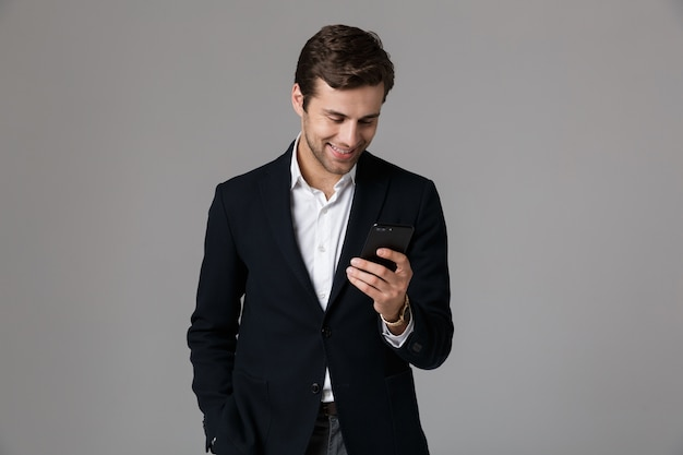 Image of smiling man 30 s en costume d'affaires à l'aide de smartphone noir, isolé sur mur gris