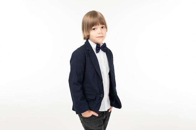 Image os un garçon adolescent en costume noir se dresse et pose isolé