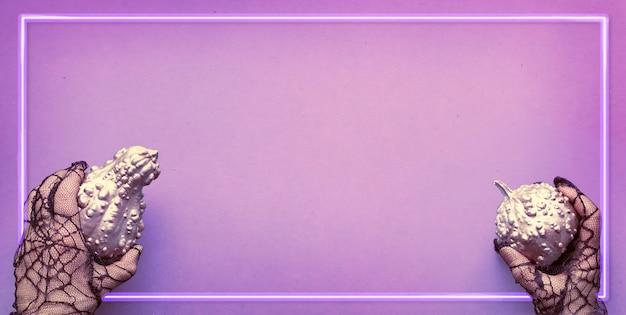 Image panoramique d'halloween avec cadre néon sur mur violet clair et copie-espace. mains en gants en maille noire tenant des citrouilles décoratives peintes en rose métallique