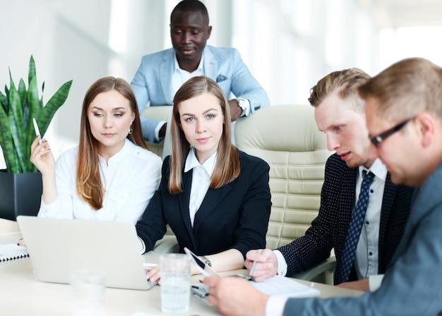 Image de partenaires commerciaux discutant de documents et d'idées lors d'une réunion