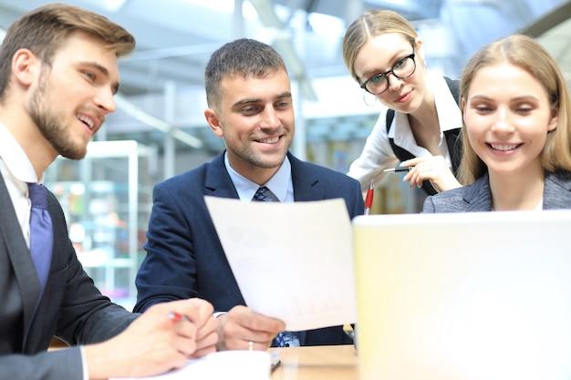 Image de partenaires commerciaux discutant de documents et d'idées lors d'une réunion.
