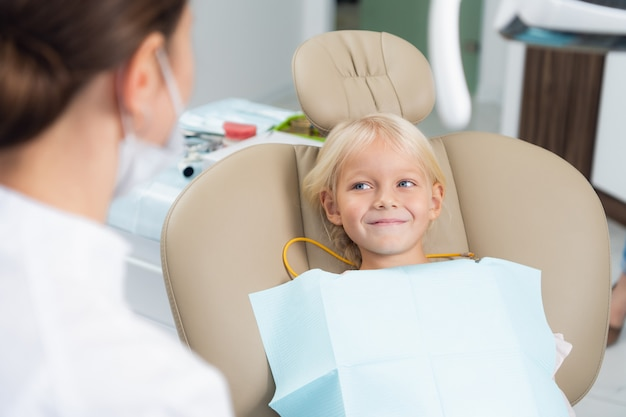 Une image d'un petit enfant de sexe féminin ayant ses dents vérifiées par un médecin