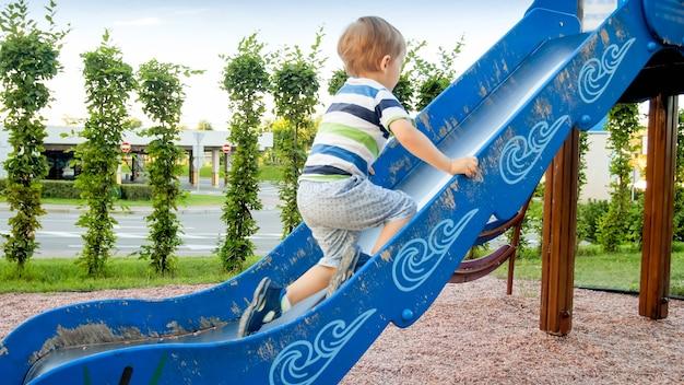 Image D'un Petit Garçon Joyeux Et Souriant Qui Monte Et Grimpe Sur La Grande Aire De Jeux Pour Enfants Du Parc Photo Premium