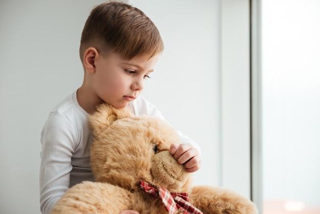 Image d'un petit garçon triste près de la fenêtre avec un ours en peluche attendant les parents à la maison. regarder de côté.