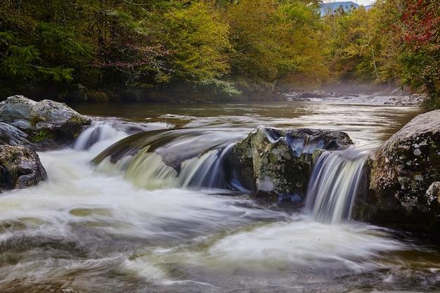 Image d'une photo de paysage d'une cascade peu profonde striant de gros rochers